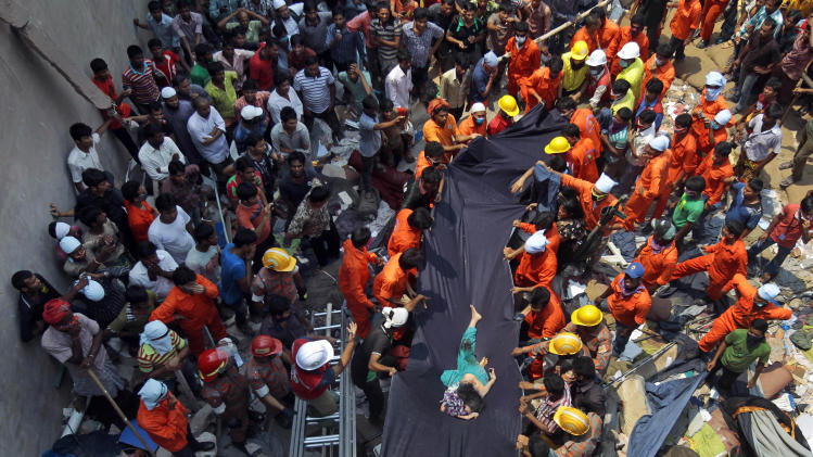 Bangladeshi people watch as rescuers use a piece of fabric to lower the body of a woman after she was discovered inside a building that collapsed Wednesday in Savar, near Dhaka, Bangladesh,Thursday, April 25, 2013. By Thursday, the death toll reached at least 194 people as rescuers continued to search for injured and missing, after a huge section of an eight-story building that housed several garment factories splintered into a pile of concrete. (AP Photo/A.M.Ahad)