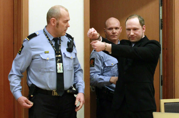 Anders Behring Breivik, right, a right-wing extremist who confessed to a bombing and mass shooting that killed 77 people on July 22, 2011, gestures as he arrives for a detention hearing at a court in