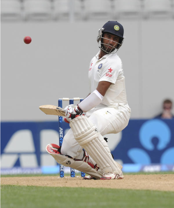 India's Cheteshwar Pujara ducks a bouncer against New Zealand on the third day of the first cricket test at Eden Park in Auckland, New Zealand, Saturday, Feb. 8, 2014. (AP Photo/SNPA, Ross Setford) NE