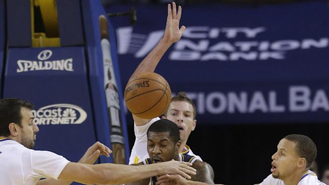 Utah Jazz power forward Derrick Favors (15) passes as he is defended by Golden State Warriors center Andrew Bogut, from left, power forward David Lee and shooting guard Stephen Curry during the first quarter of an NBA basketball game in Oakland, Calif., Saturday, Nov. 16, 2013