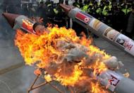 South Korean conservative activists set fire to a mock North Korean missile during a protest in Seoul on Friday. South Korea stepped up an operation Saturday to retrieve debris from North Korea's failed rocket launch, officials said, apparently in competition with Russia and China