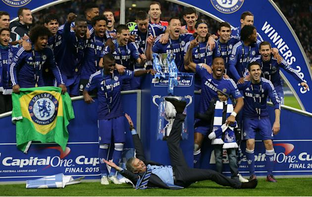 Chelsea's head coach Jose Mourinho, at front on the ground celebrates with the team after they had won the English League Cup Final between Tottenham Hotspur and Chelsea at Wembley stadium in Lond