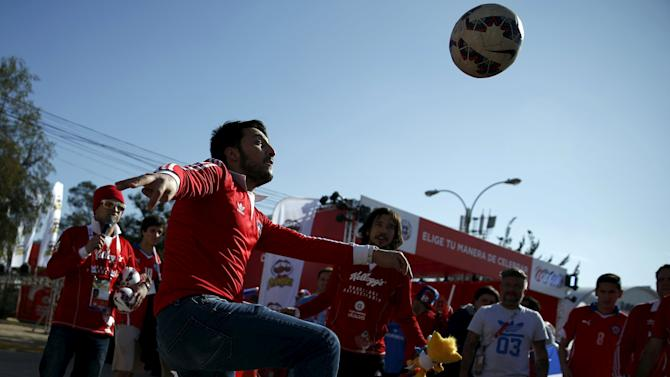 Chilean soccer fans play with a ball ahead of the Copa America 2015 final soccer match between Chile and Argentina in Santiago
