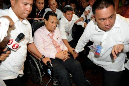 Philippines Chief Justice Renato Corona (in wheelhair) is escorted by security personnel as he leaves the Senate