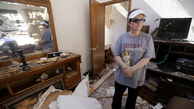 In this Wednesday, May 22, 2013 photo, Cindy Sasnett clings to a porcelain Christmas angel decoration she recovered from her destroyed home as she stands in one of the rooms she almost took refuge in from Monday's tornado, in Moore, Okla. (AP Photo/Tony Gutierrez)