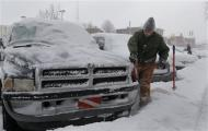 Barry Tilton cleans the snow off of his pick-up truck in the midtown neighborhood of Detroit, Michigan January 6, 2014. REUTERS/Rebecca Cook
