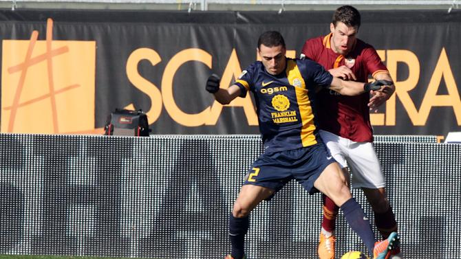 AS Roma's Kevin Strootman, right, of the Netherlands, challenges for the ball with Hellas Verona's  Romulo, of Brazil, during a Serie A soccer match at the Bentegodi stadium in Verona, Italy, Sunday, Jan. 26, 2014