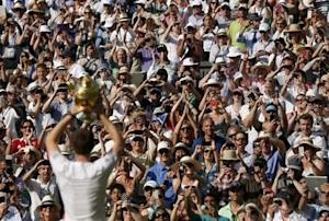 Andy Murray of Britain holds the winners trophy up to the spectators after defeating Novak Djokovic of Serbia in their men's singles final tennis match at the Wimbledon Tennis Championships, in London