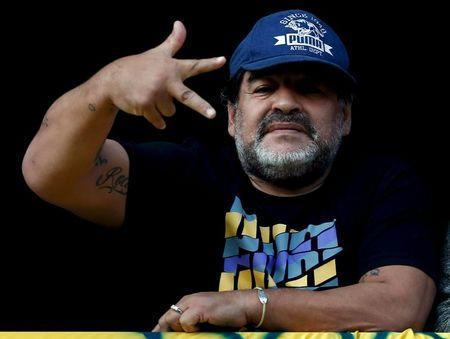 Former Argentine soccer player Maradona gestures from a balcony as he attends the Argentine First Division soccer match between Boca Juniors and Quilmes in Buenos Aires