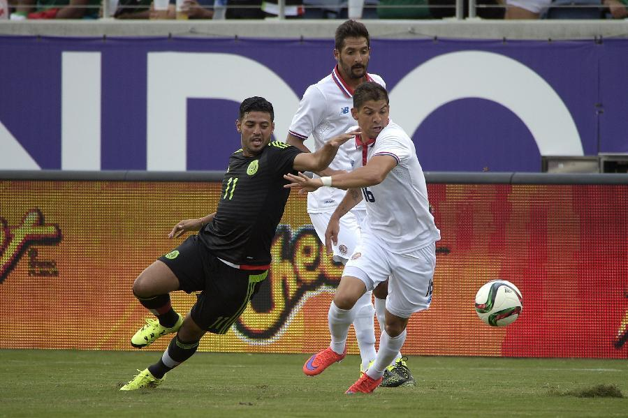 Mexico forward Carlos Vela (11) and Costa Rica defender Christian Gamboa (16) battle for the ball during the first half of a friendly soccer match in Orlando, Fla., Saturday, June 27, 2015. (AP Photo/
