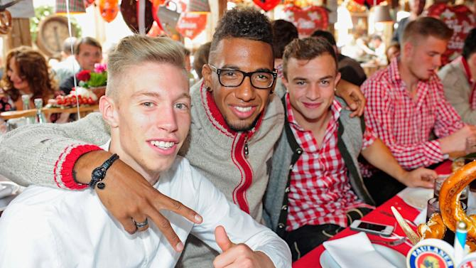 Mitchell Weiser, Jerome Boateng and Xherdan Shaqiri, from left, of Bayern Munich attend the Oktoberfest beer festival in Munich southern Germany, Sunday, Oct 6, 2013