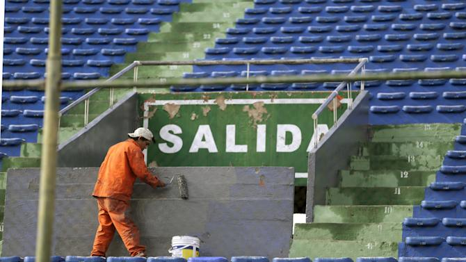 Worker paints an entrance of a stadium in Asuncion