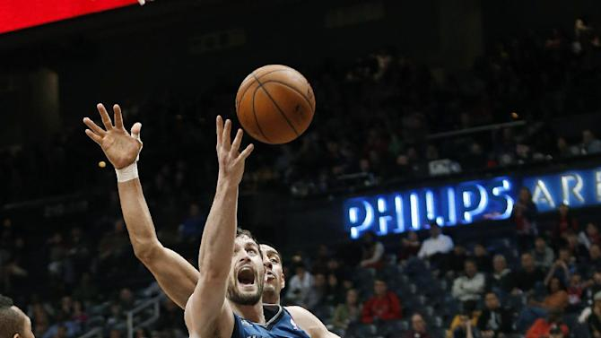 Minnesota Timberwolves forward Kevin Love (42) scores against Atlanta Hawks forward Gustavo Ayon, obscured, during the second half of an NBA basketball game Saturday, Feb. 1, 2014, in Atlanta. Atlanta won 120-113