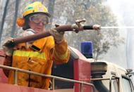 A Country Fire Authority (CFA) firewoman dampens down fire after saving houses north of Healesville near Melbourne in 2009. A class action over Australia's deadly 2009 wildfires was launched Tuesday against a Singapore power company, with victims of the blaze that killed 40 people blaming the firm for its ignition