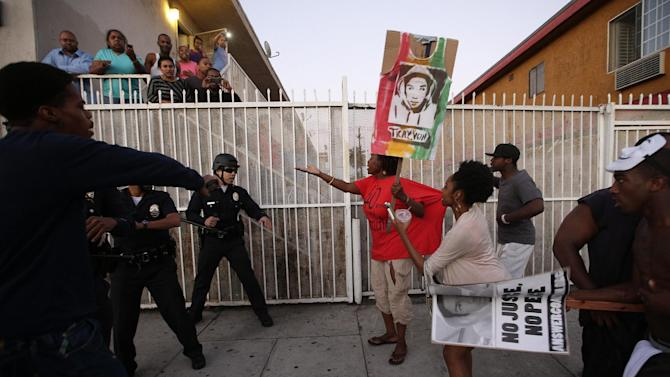 Protesters confront Los Angles police officers during a demonstration in reaction to the acquittal of neighborhood watch volunteer George Zimmerman on Monday, July 15, 2013, in Los Angeles. Anger over the acquittal of a U.S. neighborhood watch volunteer who shot dead an unarmed black teenager continued Monday, with civil rights leaders saying mostly peaceful protests will continue this weekend with vigils in dozens of cities. (AP Photo/Jae C. Hong)