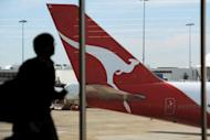 An airport passenger walks past a Qantas plane at Sydney International Airport. Qantas Airways on Wednesday severed a lucrative marketing deal with Tourism Australia after claiming its boss was leading a consortium trying to unseat the airline's management and buy out the company