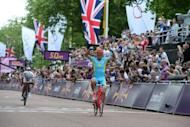 Kazakhstan's Alexandre Vinokourov celebrates as he crosses the finish line after winning the gold in the men's cycling road race at the London 2012 Olympic games on Saturday