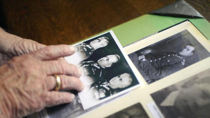 In this Friday, Sept. 7, 2012 photo, Franciszek Herzog looks at photographs of his father at his home in Hebron, Conn. Documents released Monday, Sept. 10, 2012, and seen in advance by The Associated Press lend further weight to the belief that sabotage within the highest levels of U.S. government helped cover up Soviet guilt in the killing of some 22,000 Polish officers and other prisoners in the Katyn Forest and other locations in 1940. Herzog's father and uncle both died in the massacres. (AP Photo/Jessica Hill)