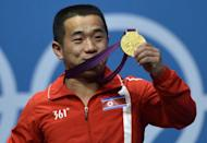 North Korea's Om Yun Chol celebrates with his gold medal on the podium for the weightlifting men's 56kg at the Excel Center in London during the 2012 London Olympic Games