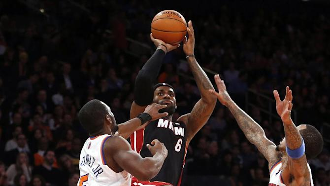 Miami Heat's LeBron James (6) shoots against New York Knicks' Tim Hardaway Jr. (5) and J.R. Smith during the second half of an NBA basketball game Saturday, Feb. 1, 2014, in New York.  Miami won 106-91