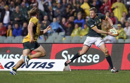 De Villiers of South Africa's Springboks passes the ball under pressure from Hooper of Australia's Wallabies during their Tri-Nations Rugby Union match at Subiaco Oval in Perth