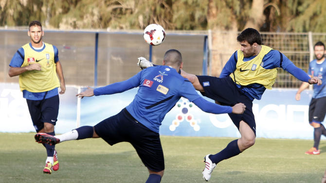 Greece's Sokratis Papastathopoulos, right, stops the ball in front of Kostas Mitroglou during a training session in Athens, Monday, Oct. 14, 2013, ahead of their 2014 World Cup Group G qualifying match against Liechtenstein on Tuesday