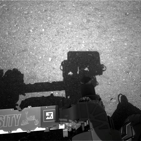 This is the first image taken by the Navigation cameras on NASA's Curiosity rover. It shows the shadow of the rover's now-upright mast in the center, and the arm's shadow at left. The arm itself can be seen in the foreground. Image released Aug