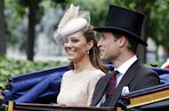 """Britain's Prince William and his wife Kate, Duchess of Cambridge take an open top carriage ride through the streets of London after a Diamond Jubilee Luncheon given for The Queen, Tuesday June 5, 2012 . Crowds cheering """"God save the queen!"""" and pealing church bells greeted Queen Elizabeth II on Tuesday as she arrived for a service at St. Paul's Cathedral on the last of four days of celebrations of her 60 years on the throne. (AP Photo/Peter Byrne/Pool)"""