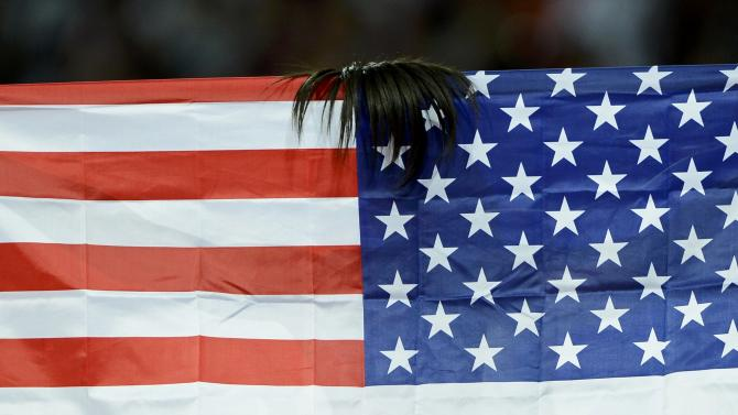 Part of Allyson Felix's hair is seen on top of her national flag, the U.S. flag, as she celebrates winning gold in the women's 200m final during the London 2012 Olympic Games