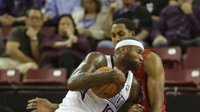 Sacramento Kings center DeMarcus Cousins, left, drives to the basket against Los Angeles Clippers center Ryan Hollins during the first  quarter of an NBA preseason basketball game in Sacramento, Calif., Monday, Oct. 14, 2013