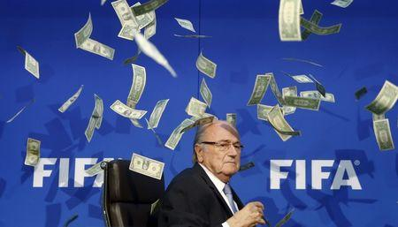 British comedian known as Lee Nelson (unseen) throws banknotes at FIFA President Blatter as he arrives for a news conference after the Extraordinary FIFA Executive Committee Meeting at the FIFA headquarters in Zurich