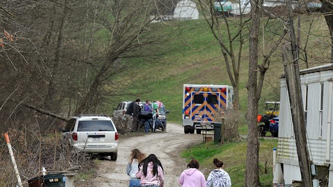 """FILE - In this April 1, 2013 file photo, Friends and neighbors walk up and down the gravel road leading to Shain Gandee's home in Sissonville, W.Va. Gandee, star of the MTV show """"Buckwild""""; his uncle, David Gandee; and Donald Robert Myers were found dead in the family's Ford Bronco Monday morning. Shain Gandee died doing what made him famous: careening through huge mudholes in his SUV, taking chances most others won't, living free and reckless in front of reality-show TV cameras. His death further blurs the line between entertainment and real life in an age where fame is easier than ever to attain.(AP Photo/The Charleston Gazette, Chip Ellis, File)"""