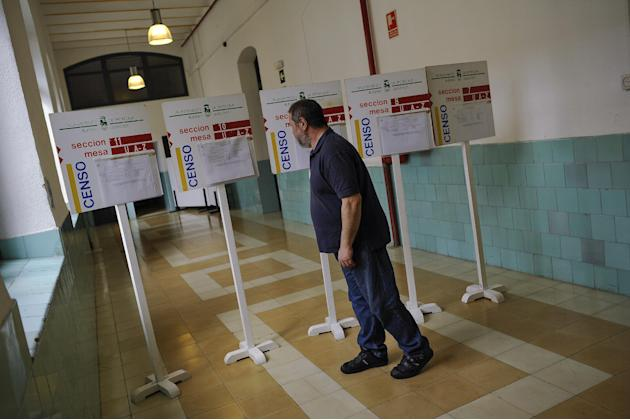 A man checks a list before voting a polling station, in Pamplona northern Spain, Sunday, May 24, 2015.  Spain could be set for a political upheaval in key local elections on May 24, with strong signs