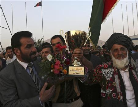 Afghan cricket team captain Mohammad Nabi Esa Khil (C) holds the ACC Cup after the team's arrival in Kabul, October 12, 2013, following Afghanistan's qualification for the 2015 Cricket World Cup. REUT