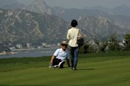 Chinese tourists pose for photos at a golf course which has been closed for over three years at the Mount Kumgang international tourist zone in North Korea on September 1, 2011. Foreigners visiting North Korea can now take their own mobile phones into the country, Chinese state media reported Sunday, citing an employee with the operator of the country's mobile network.
