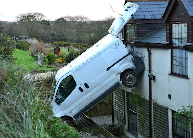"""A white van man is lucky to be alive after he crashed his motor, flipping it and landing it vertically against a hotel near Newquay, Cornwall. Luckily no one was hurt. Simon Hill, owner of the White House Inn said: """"It could have been very dangerous if there had been someone in that room. They would certainly have got a shock."""" (SWNS)"""