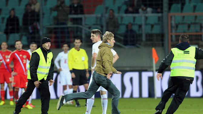 A man runs over the pitch as security try to catch him, during the World Cup 2014 Group F qualifying soccer match between Luxembourg and  Russia,  in Luxembourg city, at the Josy Barthel stadium, Friday, Oct. 11, 2013
