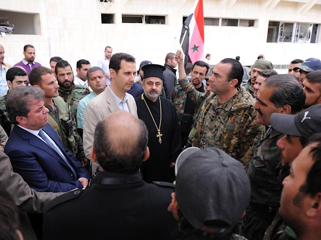 Syrian President Bashar al-Assad talks to soldiers during his visit to Maaloula