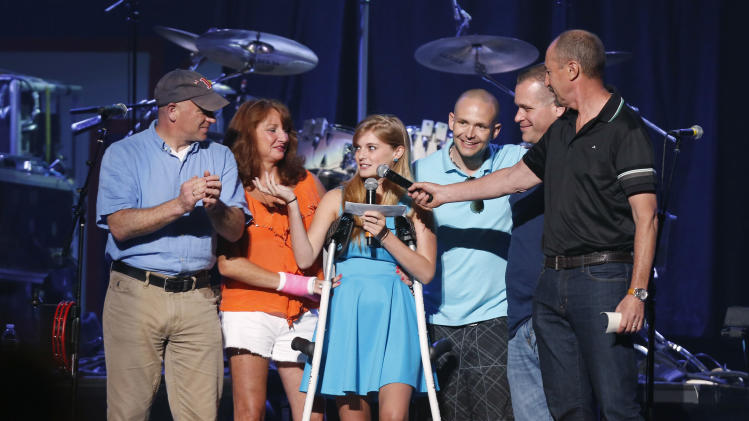 Boston Marathon bombing victim Victoria McGrath, 20, center, thanks people who help her when she was injured and help her recovery during the Boston Strong Concert: An Evening of Support and Celebration at the TD Garden on Thursday, May 30, 2013 in Boston. (Photo by Bizuayehu Tesfaye/Invision/AP)