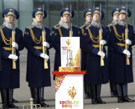 An honour guard salutes as the Olympic flame stands on display after arriving in Moscow