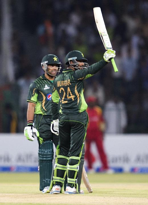 Pakistan's Mukhtar Ahmed, right, acknowledges his fifty with Umar Akmal during a match at the Gaddafi Stadium in Lahore, Pakistan, Sunday, May 24, 2015. The Twenty20 matches Friday and Sunday mark
