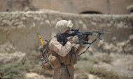 A US Marine is seen on patrol in Helmand Province in June. Two US Marines have been referred to trial by courts martial for urinating on the bodies of Taliban dead in Afghanistan and posing for photographs with them, the Pentagon said