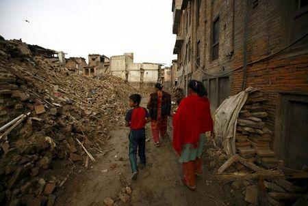 People walk past collapsed houses that were damaged during the earthquake in Bhaktapur