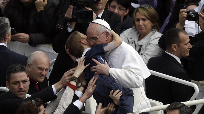 Pope Francis hugs a child after celebrating his first Easter Mass in St. Peter's Square at the Vatican, Sunday, March 31, 2013. Pope Francis celebrated his first Easter Sunday Mass as pontiff in St. Peter's Square, packed by joyous pilgrims, tourists and Romans and bedecked by spring flowers.Wearing cream-colored vestments, Francis strode onto the esplanade in front of St. Peter's Basilica and took his place at an altar set up under a white canopy. (AP Photo/Gregorio Borgia)