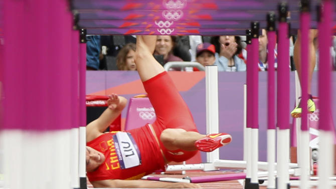 China's Liu Xiang falls after crashing into the first hurdle during his men's 110m hurdles round 1 heat at the London 2012 Olympic Games at the Olympic Stadium