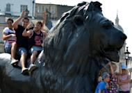 Tourists sit on a lion statue as they pose for photos at Trafalgar Square in central London. Prime Minister David Cameron insisted Thursday that Britain would deliver a memorable Olympics after US presidential hopeful Mitt Romney backtracked on barbed comments he made about the London Games