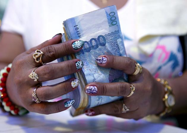 File photo of a casino financier wearing rings and with painted fingernails, counting money she collected from a gambler only moments before, in Angeles city