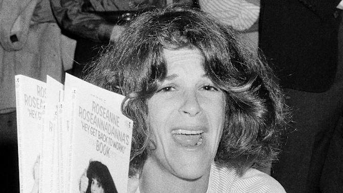 "FILE - In this Sept. 27, 1983 file photo, actress and comedienne Gilda Radner holds up copies of her book, ""Roseanne Roseannadanna's  ""Hey, Get Back To Work,"" at a New York bookstore. The Madison, Wis.-area chapter of Gilda's Club  is the latest to change its name to the Cancer Support Community, a move its director said was necessary because young people don't know who Radner was.  (AP Photo/Suzanne Vlamis)"