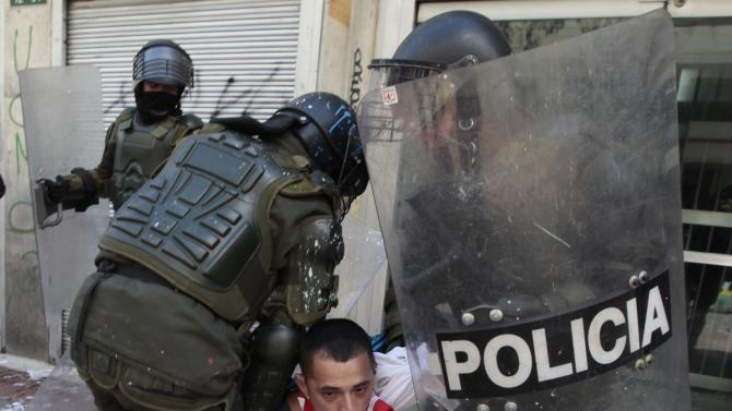 Riot police detain a protester during a protest against agricultural and trade policies in Bogota
