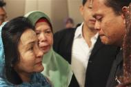 Rosmah Mansor (L), wife of Malaysian Prime Minister Najib Razak, cries with family members of passengers on the missing Malaysia Airlines flight MH370, at a hotel in Putrajaya March 9, 2014. REUTERS/Zulfadli Zaki